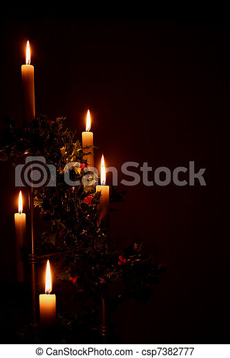 lit christmas holiday candles with holly - csp7382777