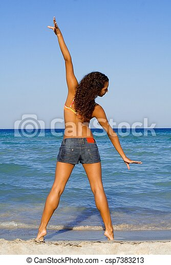young woman doing stretching exercises on beach - csp7383213