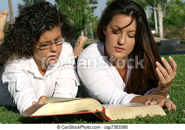 youth or teens reading book or bible outdoors - csp7383386