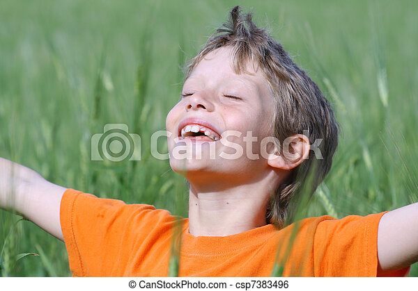 happy smiling child arms outstretched eyes closed enjoying the summer sun - csp7383496