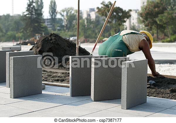 A worker puts exterior tiles  - csp7387177