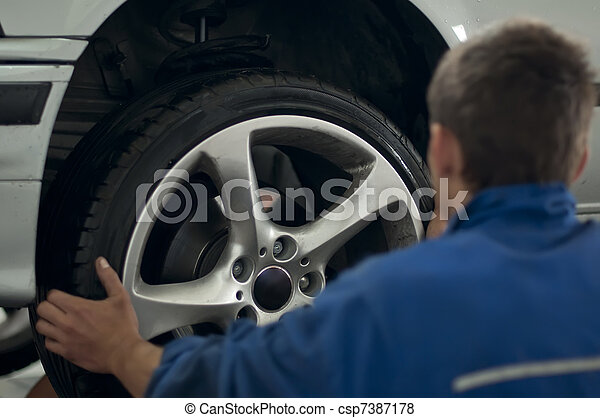Mechanic put a car tire - csp7387178