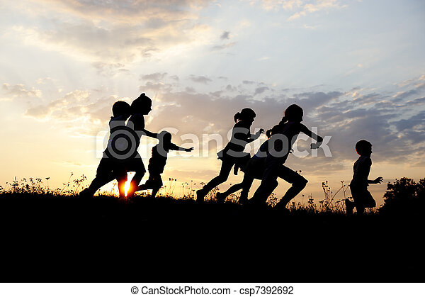 Silhouette, group of happy children playing on meadow, sunset, summertime - csp7392692