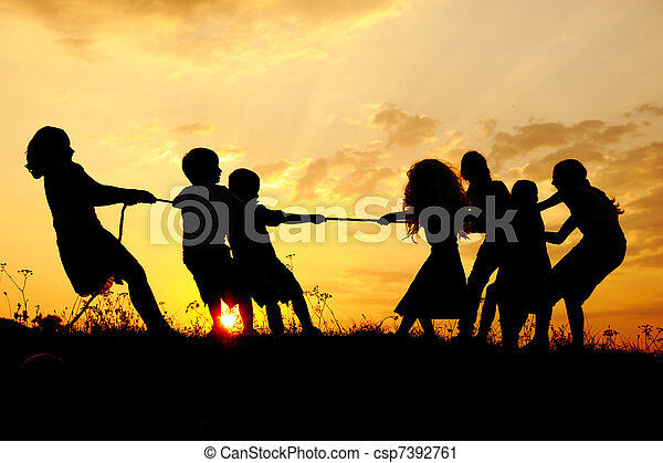 Silhouette, group of happy children playing on meadow, sunset, summertime - csp7392761