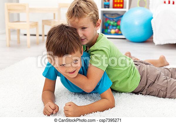 Kids wrestling on the floor - csp7395271
