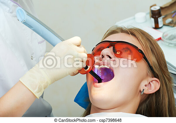 dental filing of child tooth by ultraviolet light - csp7398648