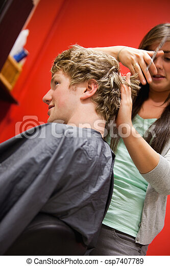 Portrait of a serious woman cutting a man's hair - csp7407789