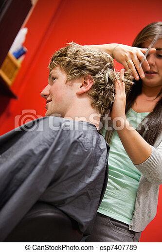 Portrait of a serious woman cutting a man's hair - csp7407789
