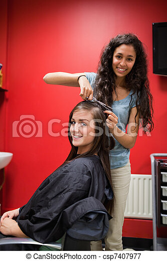 Portrait of a happy hairdresser cutting hair - csp7407977