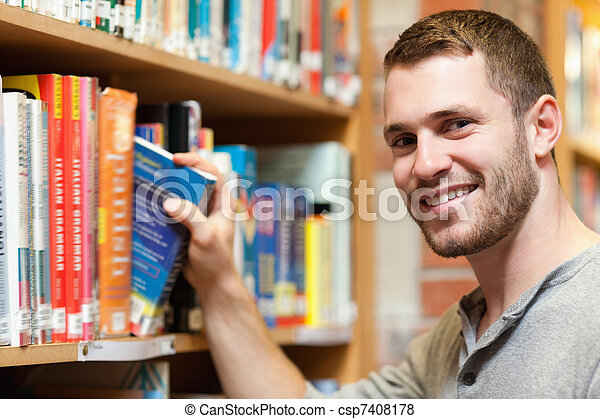 Smiling male student picking a book - csp7408178