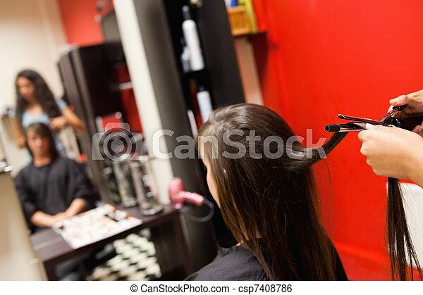 Cute woman having her hair straightened - csp7408786