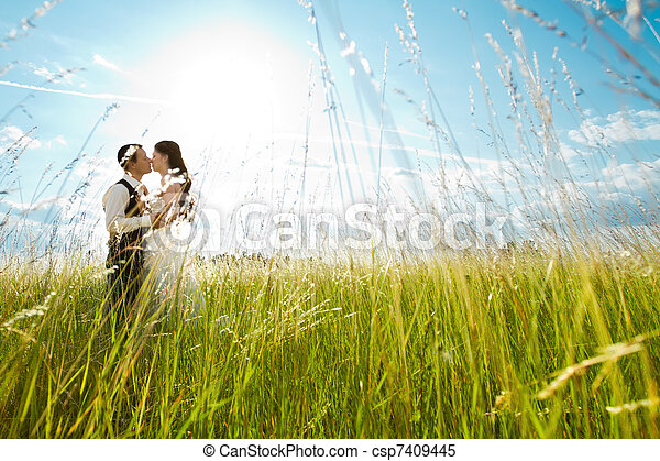 Kissing bride and groom in sunny grass - csp7409445