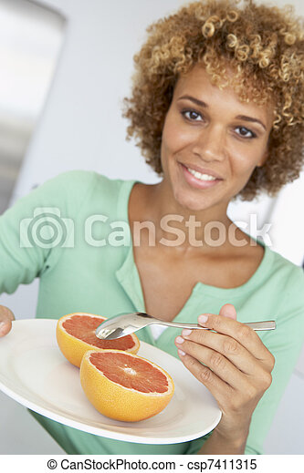 Mid Adult Woman Eating Fresh Grapefruit - csp7411315