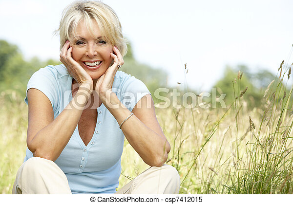 Portrait of mature woman sitting in countryside - csp7412015