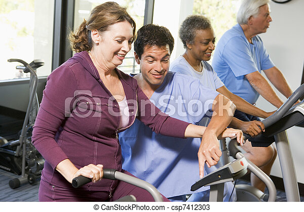 Nurse With Patient In Rehabilitation Using Exercise Machine - csp7412303