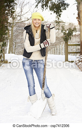 Teenage Girl Clearing Snow From Drive - csp7412306