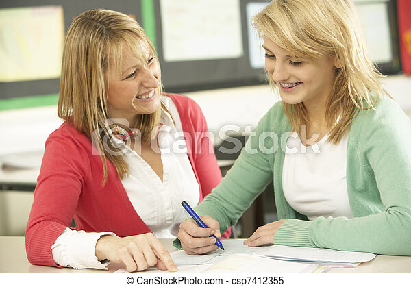 Female Teenage Student Studying In Classroom With Teacher - csp7412355