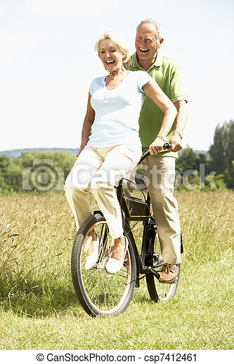 Mature couple riding bike in countryside - csp7412461