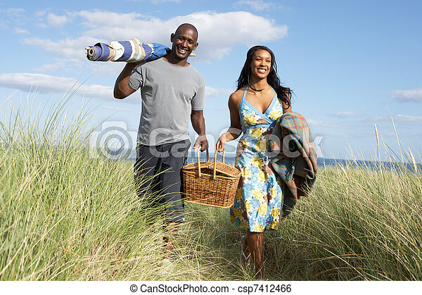 Young Couple Carrying Picnic Basket And Windbreak Walking Through Dunes - csp7412466
