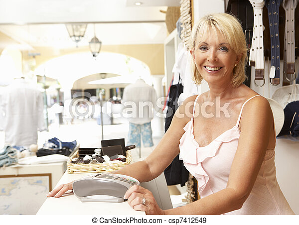 Female Sales Assistant At Checkout Of Clothing Store - csp7412549