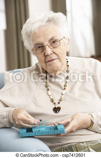 Senior Woman Sorting Medication Using Organiser At Home - csp7412601