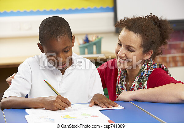 Schoolboy Studying In Classroom With Teacher - csp7413091
