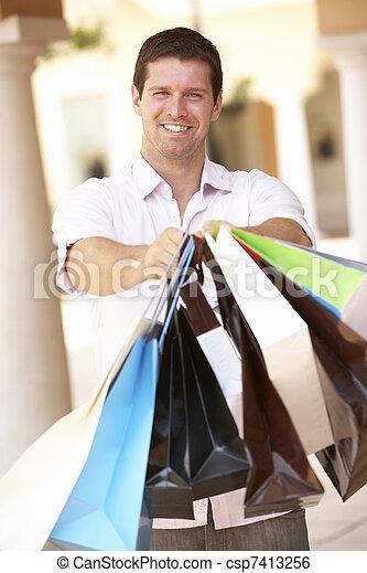 Young Man Enjoying Shopping Trip - csp7413256