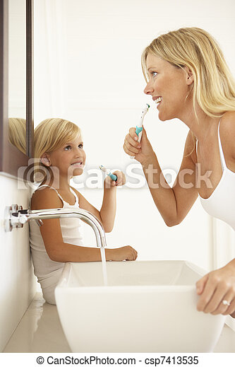 Mother And Daughter Brushing Teeth In Bathroom Together - csp7413535