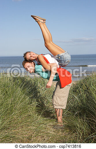 Energetic Young Couple Having Fun In Dunes By Beach - csp7413816