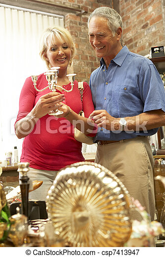 Middle aged couple shopping for antiques - csp7413947