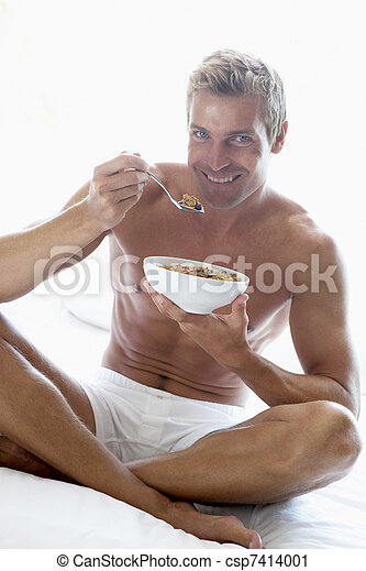 Mid Adult Man Eating A Bowl Of Cereal - csp7414001