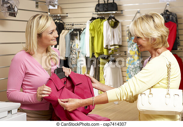 Sales assistant with customer in clothing store - csp7414307