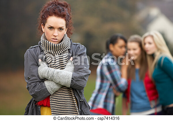 Upset Teenage Girl With Friends Gossiping In Background - csp7414316