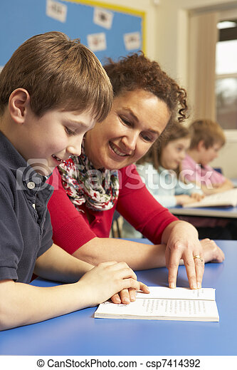 Schoolboy Studying In Classroom With Teacher - csp7414392
