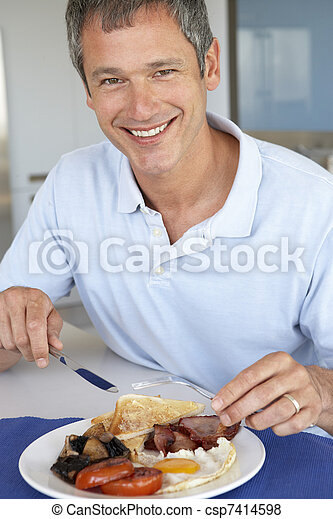 Middle Aged Man Eating Unhealthy Fried Breakfast - csp7414598