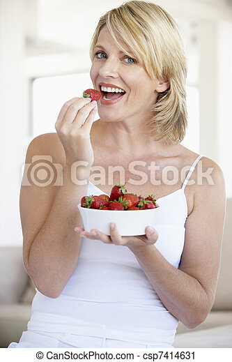 Mid Adult Woman Eating A Bowl Of Strawberries - csp7414631