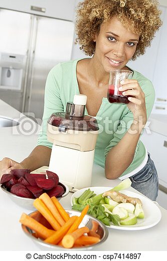 Mid Adult Woman Making Fresh Vegetable Juice - csp7414897