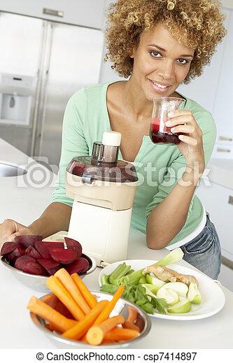 Mid Adult Woman Making Fresh Vegetable Juice - csp7414897