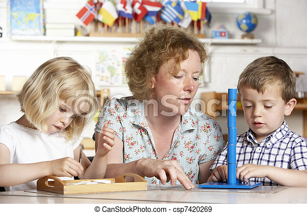 Adult Helping Two Young Children at Montessori/Pre-School - csp7420269