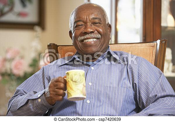 Senior man drinking hot beverage - csp7420639