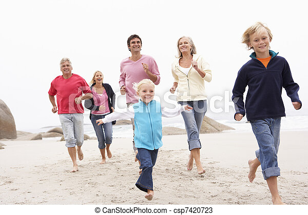 Three Generation Family Running Along Winter Beach Together - csp7420723