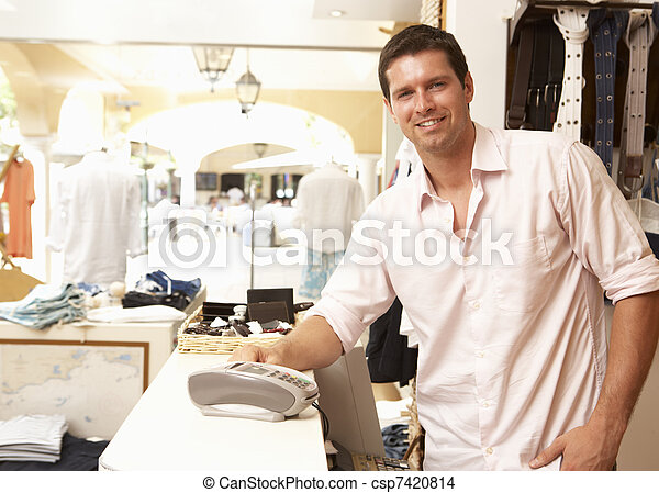 Male Sales Assistant At Checkout Of Clothing Store - csp7420814