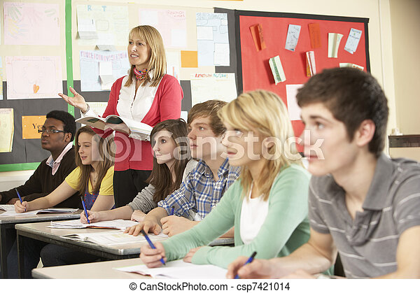 Teenage Students Studying In Classroom With Teacher - csp7421014