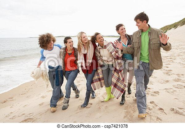 Group Of Young Friends Walking Along Autumn Shoreline - csp7421078