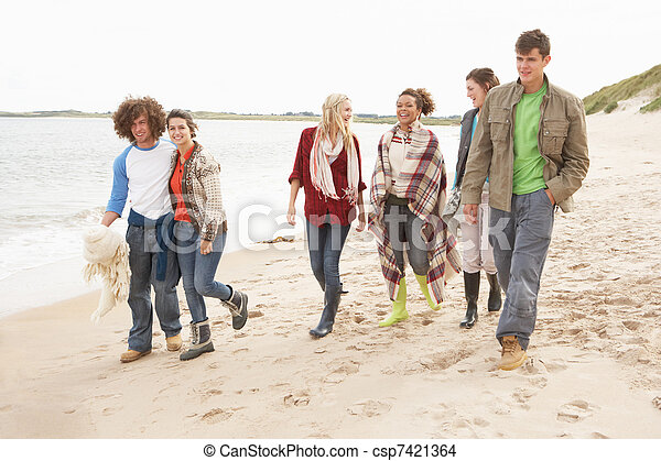 Group Of Young Friends Walking Along Autumn Shoreline - csp7421364