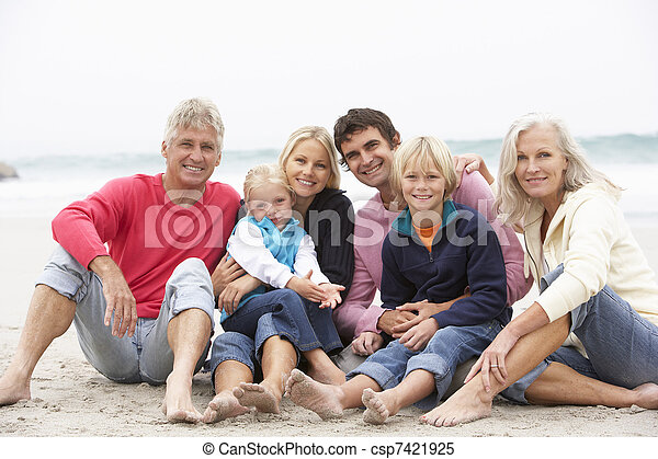 Three Generation Family Sitting On Winter Beach Together - csp7421925