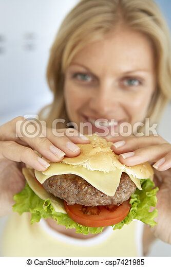 Mid Adult Woman Holding A Hamburger, Smiling At The Camera - csp7421985