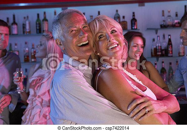 Senior Couple Having Fun In Busy Bar - csp7422014