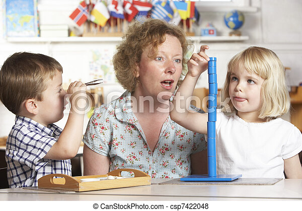 Adult Helping Two Young Children at Montessori/Pre-School - csp7422048