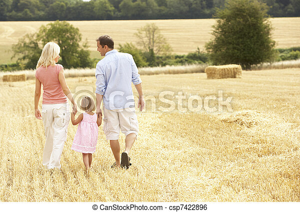 Family Walking Together Through Summer Harvested Field - csp7422896